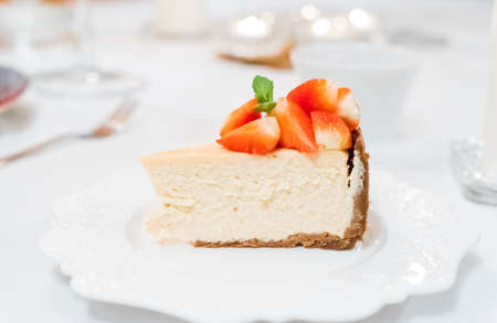 Cheesecake with strawberries and mint leaves on a white plate