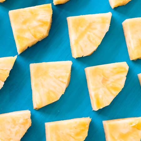 De lente of de zomerconcept: Sluit omhoog geklets van vele stukken van gele ananas die op blauwe houten lijstachtergrond leggen.