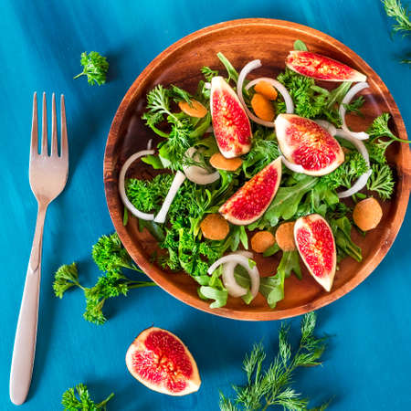Autumn salad of arugula, figs in a brown earthenware plate on a blue background. top view Stock Photo