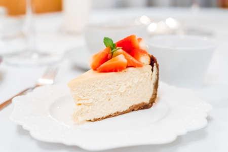 딸기와 민트 잎 하얀 접시에 치즈 케이크가 까이 서