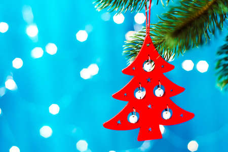 Red Christmas tree in the shape of a Christmas tree on a blue background with a bokeh on blurred, sparkling and fairy background