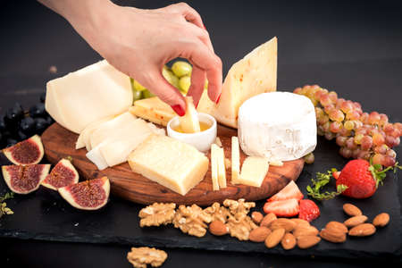 Cheese, honey and fruit on a table. Selective focus. Copy space.