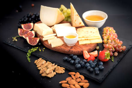 gressins: Cheese, honey and fruit on a table. Selective focus. Copy space.