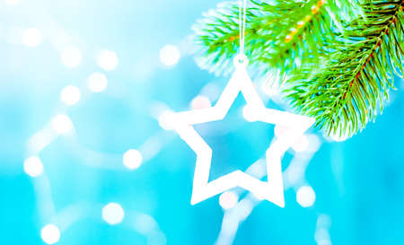 christmas star hanging from tree isolated on blue background Stock Photo