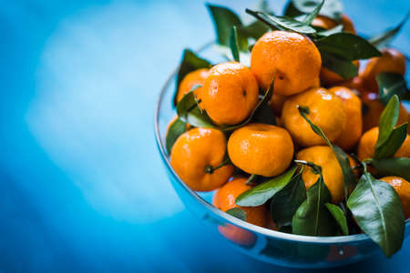 Fresh picked mandarins in a bowl on a blue background