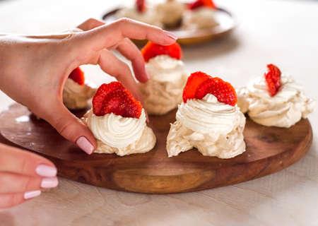A small meringue Pavlova dessert with strawberry slices garnished on blue background.
