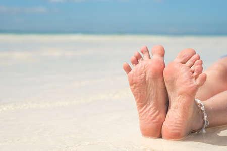 Bare feet on the sandy white beach.
