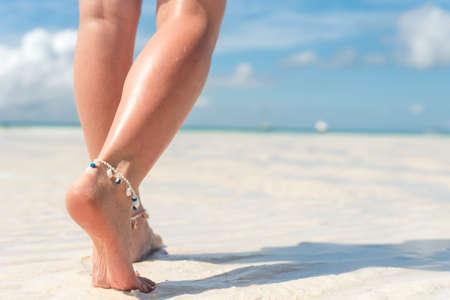 Beach travel concept. Sexy Legs on Tropical Sand Beach. Walking Female Feet.