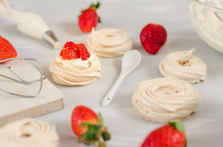 Strawberry pavlova cake nests, meringue decoration on culinary table