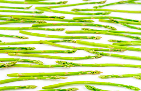 Fresh green asparagus shoots pattern, top view. Isolated over white. Food background asparagus flat lay