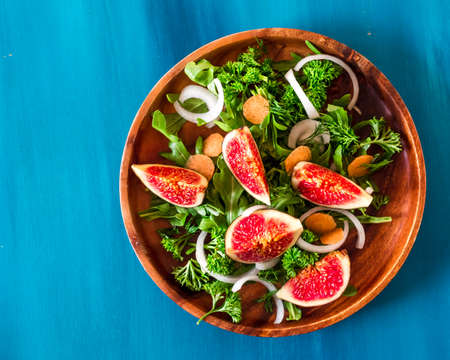 Autumn salad of arugula, figs in brown earthenware plate on a blue background. top view Stockfoto