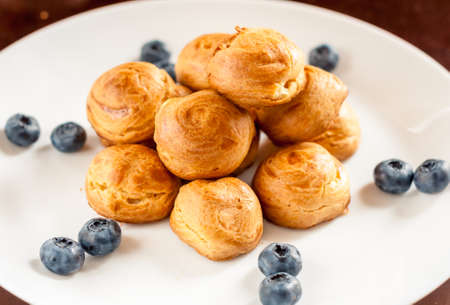 Delicious profiteroles with cream on a plate.