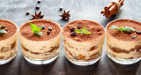 exquisite Italian dessert tiramisu decorated with mint on a dark wooden background