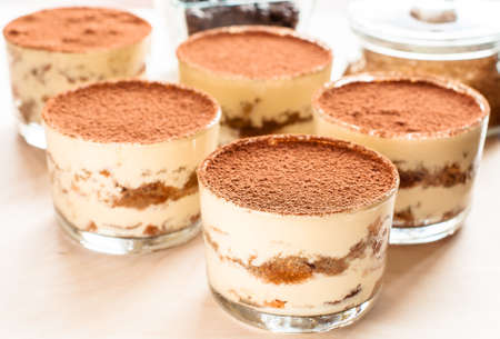 Homemade tiramisu, traditional Italian dessert in glass on wooden table