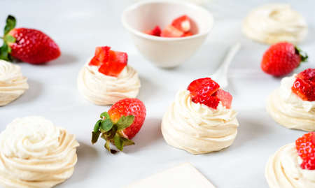 A small meringue Pavlova dessert with some strawberry slices . Top view. Pattern