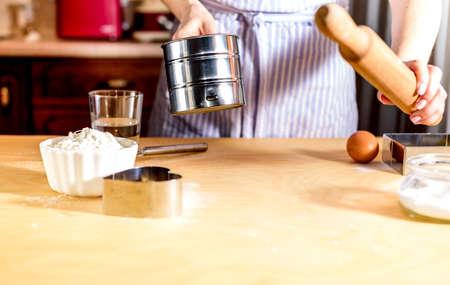 Woman sifting flour through sieve. Prepares the dough