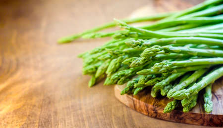 Asparagus, a bunch of fresh asparagus, on a wooden cutting board made of olive wood