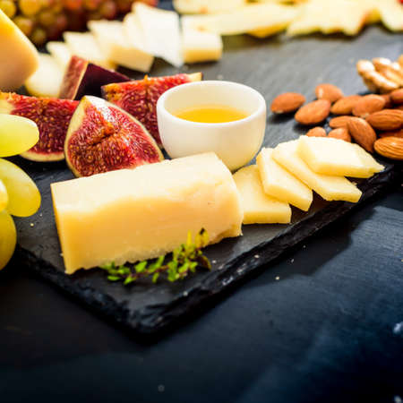 Cheese plate. Assortment of cheese with walnuts, almonds, grapes, figs, strawberries blueberries and honey