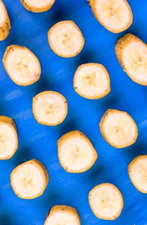 banana pattern sliced banana slices on blue horizontal Stock Photo
