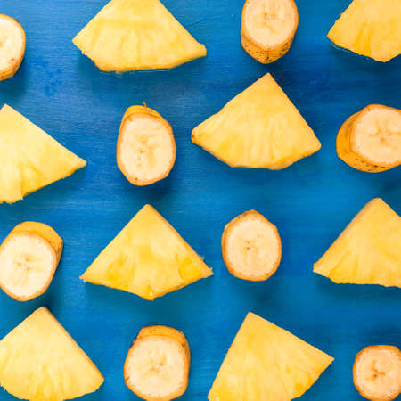 banana , pineapple pattern sliced banana slices on blue, top view Stock Photo
