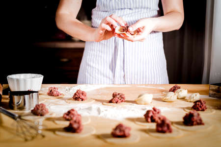 woman makes dumplings at home on kitchen table Stockfoto - 99665499