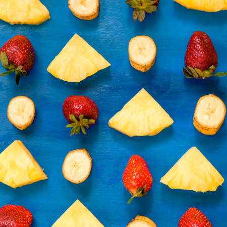 banana, pineapple, strawberry pattern sliced on blue Stock Photo
