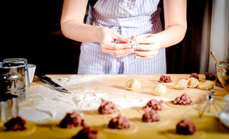 woman makes dumplings at home on kitchen table Stockfoto - 100866204