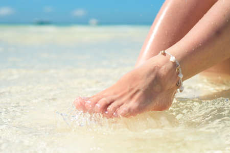 feet of a woman in the spray of clean sea water.