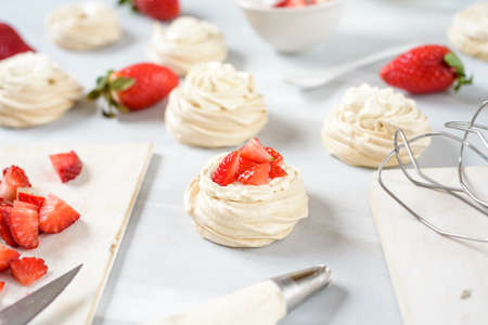 A small meringue Pavlova dessert with some strawberry slices . Top view. Imagens