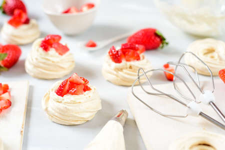 A small meringue Pavlova dessert with some strawberry slices . Top view. Stock Photo