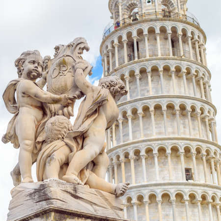 Marble statue in front of the Leaning Tower of Pisa in Piazza dei Miracoli.
