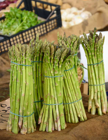 Bunches of asparagus at a farmers market.
