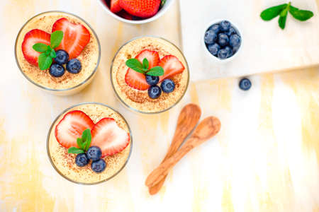 homemade, exquisite dessert tiramisu in glasses decorated with strawberry, blueberry, mint on white wooden table, Stock Photo