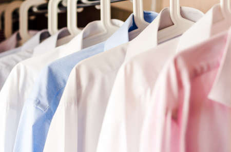 blurred background of row of white shirt hanging in closet Reklamní fotografie - 104446902