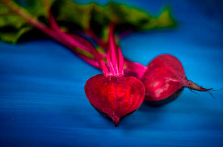 Beetroot cut in half on a blue background, place for text, healthy food Copy space. Top view.