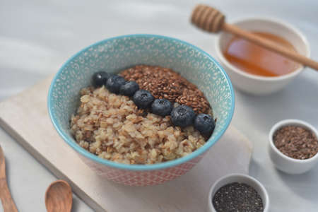 Buckwheat porridge in a bowl with flax seeds and blueberries. oncept healthy food, detox, diet Stock Photo - 105695991