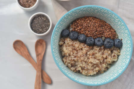 Buckwheat porridge in a bowl with flax seeds and blueberries. oncept healthy food, detox, diet