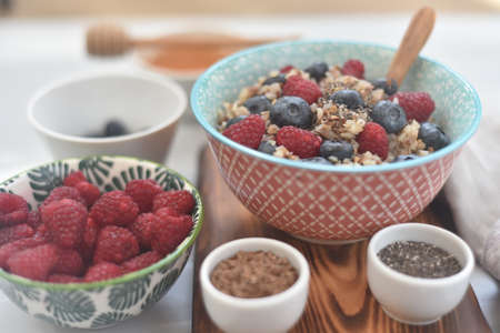 buckwheat cereal with raspberries and blueberries for breakfast, seeded with chia seeds and flax seeds, with honey, concept detox