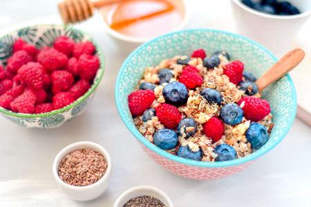 High protein healthy breakfast, buckwheat porridge with blueberries, raspberries, flax seeds and honey Closeup view Stock Photo