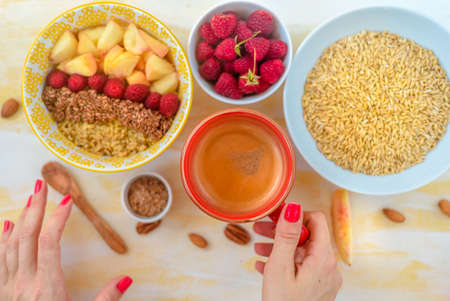 Top view, female hands holding a cup of coffee, a spoon with oatmeal, with honey nuts, raspberries, on a yellow wooden table Good morning -