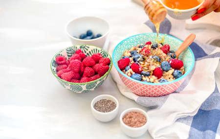 High protein healthy breakfast, buckwheat porridge with blueberries, raspberries, flax seeds and honey Closeup view Stock Photo - 106778755