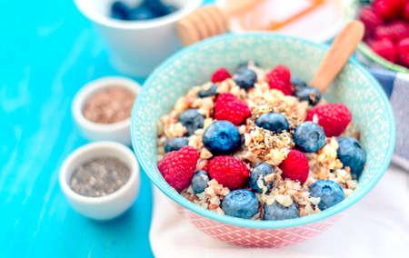 High protein healthy breakfast, buckwheat porridge with blueberries, raspberries, flax seeds and honey Closeup view Stock Photo - 107217362