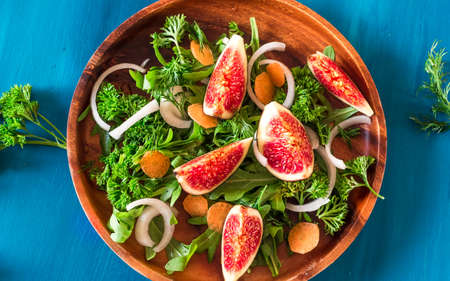 Autumn salad of arugula, figs in brown earthenware plate on a blue background. top view Stock Photo