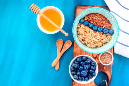 Buckwheat porridge in a bowl with flax seeds and blueberries. oncept healthy food, detox, diet, breakfast, top view Stock Photo