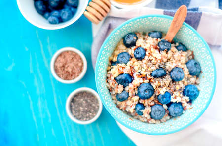 High protein healthy breakfast, buckwheat porridge with blueberries, flax seeds and honey