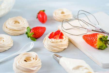 Strawberry PavlovaHomemade small strawberry pavlova meringue cakes with cream dessert with fresh mint