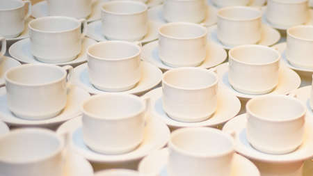 empty coffee cups with saucers pattern waiting for the visitors of the meeting