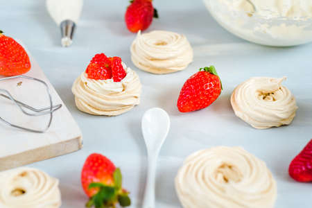 Strawberry pavlova cake nests, meringue decoration on a culinary table Stock Photo