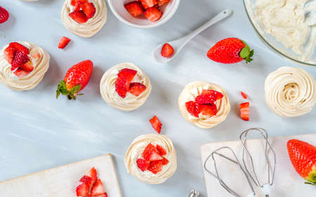 Homemade small strawberry pavlova meringue cakes pattern with cream top view