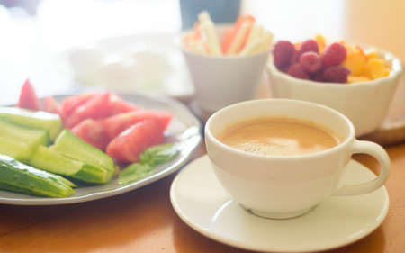 Breakfast with coffee, egg, vegetables and fruits
